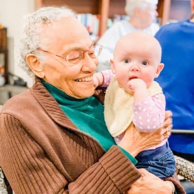 A resident holding a baby near Arbor Glen Senior Living in Lake Elmo, Minnesota
