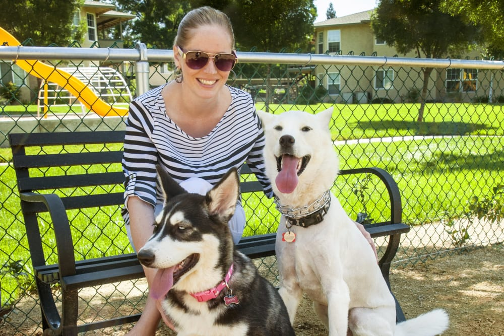 Resident and her two dogs hanging out by the dog park at Oak Meadow Apartments in Chico, California