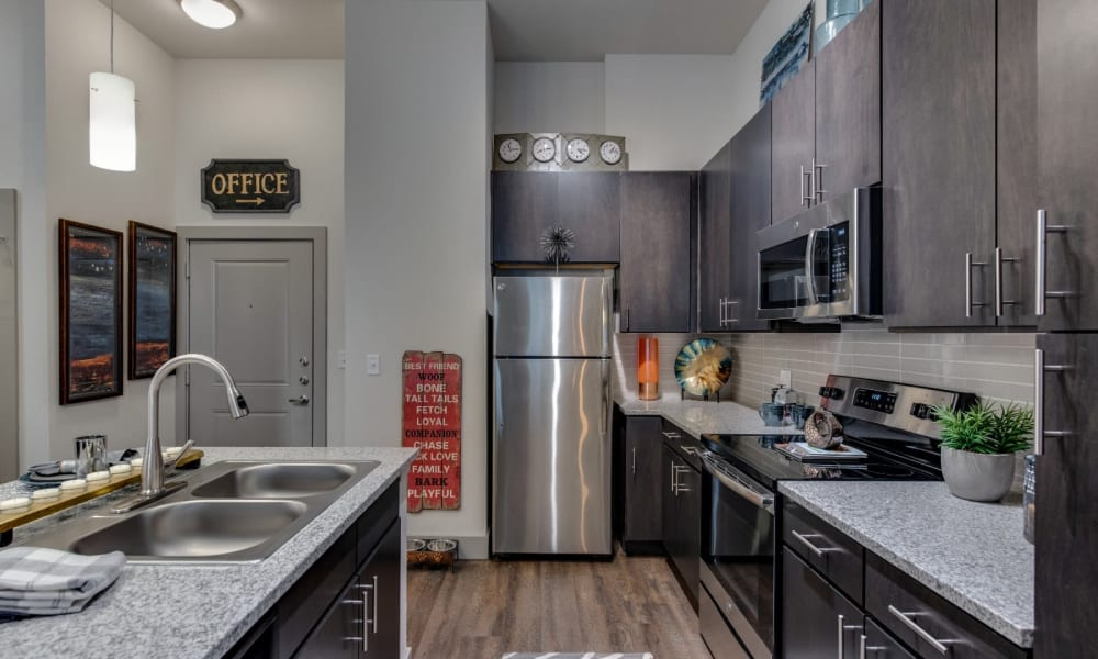 Large kitchen with stainless steel appliances and wood style flooring at Bellrock Upper North in Haltom City, Texas