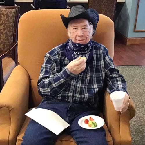 Resident dressed like a cowboy eating in a lounge at Oxford Glen Memory Care at Grand Prairie in Grand Prairie, Texas