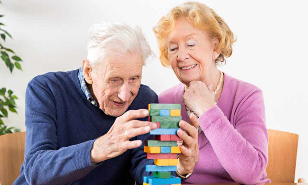 Senior couple playing jenga at The Phoenix at Lady's Island in Beaufort, South Carolina