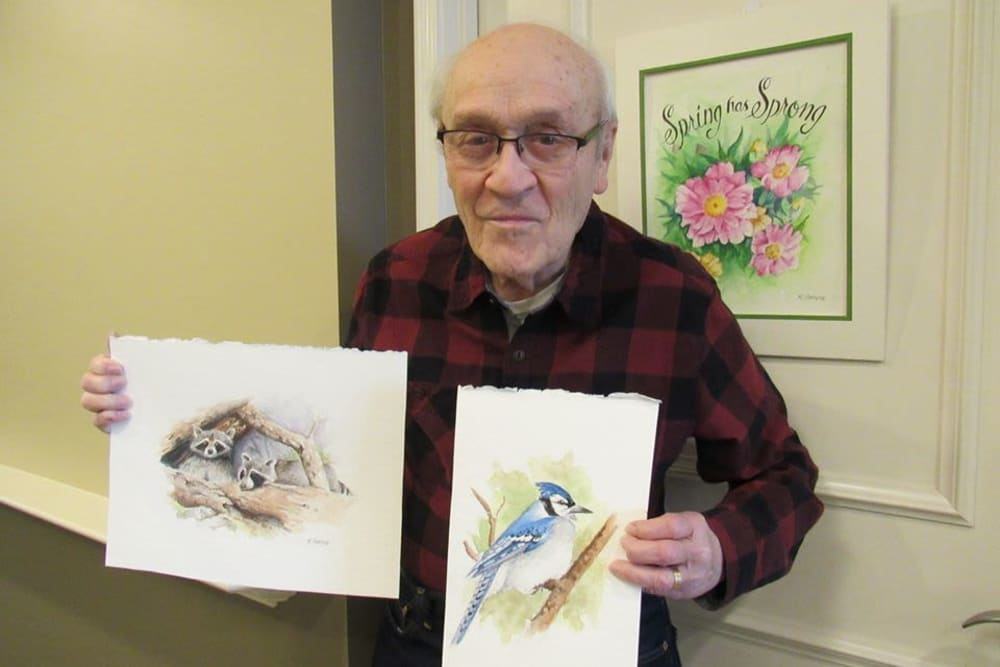 Resident with his paintings at Aspired Living of Westmont