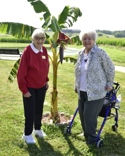 Residents out on a walk taking a picture with a tall plant at Garden Place Columbia in Columbia, Illinois.