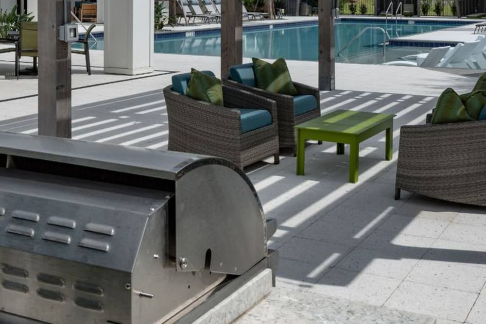 Outdoor grilling area with seating and places to cook poolside at Reunion at 400 in Kissimmee, Florida