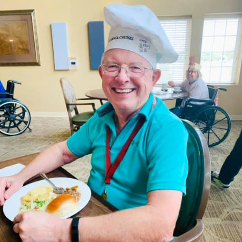 Resident seated in front of a meal, wearing a chefs cap at The Oxford Grand Assisted Living & Memory Care in McKinney, Texas
