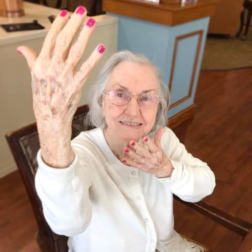 Resident showing off her painted nails at Oxford Glen Memory Care at Grand Prairie in Grand Prairie, Texas