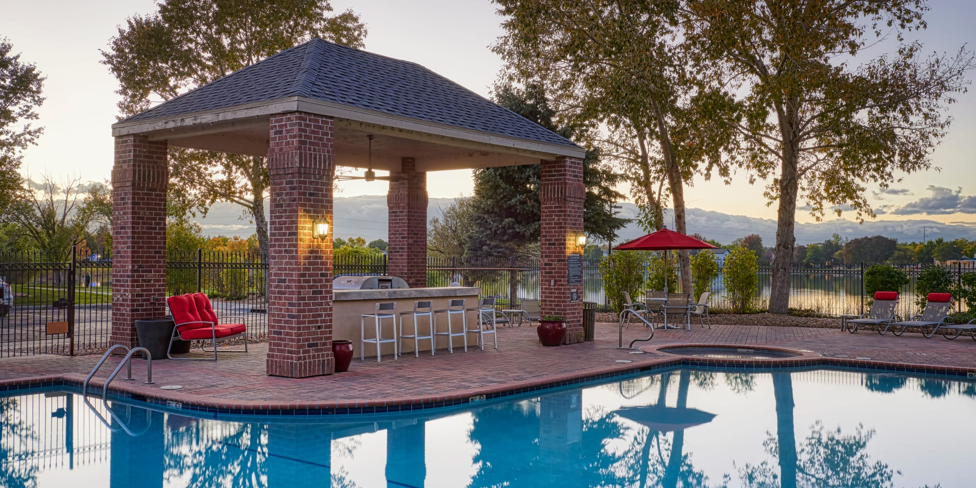 Poolside sunrise view of covered BBQ and lake in Thornton, CO