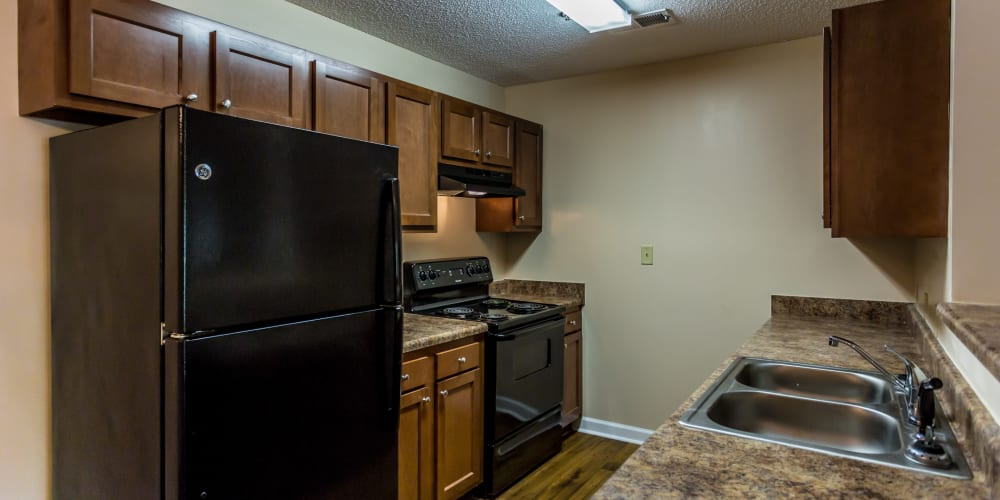 Brown cabinets and black appliances in a kitchen at Park Ridge Apartments in Jackson, Tennessee