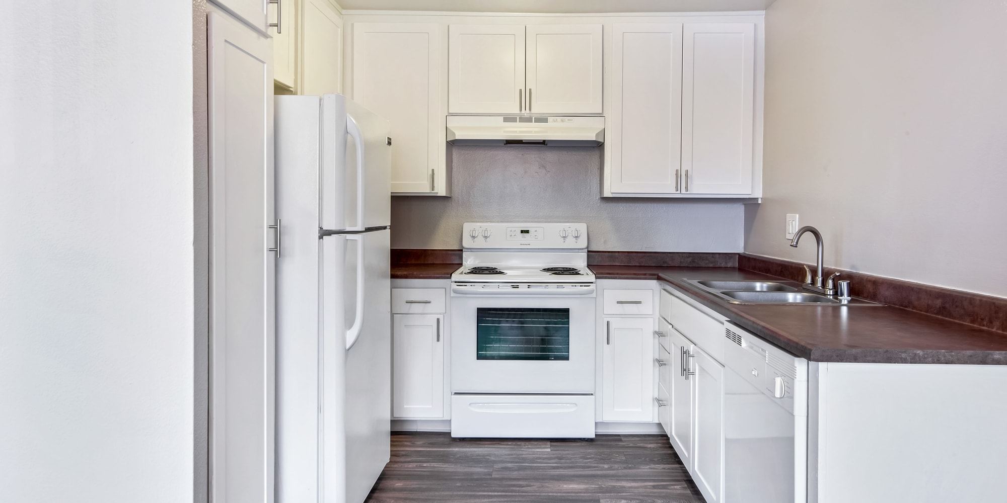 Kitchen with white appliances at West Fifth Apartments in Ontario, California