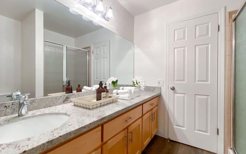 Model home's spacious primary bathroom with a granite countertop and large vanity mirror at Pleasanton Glen Apartment Homes in Pleasanton, California