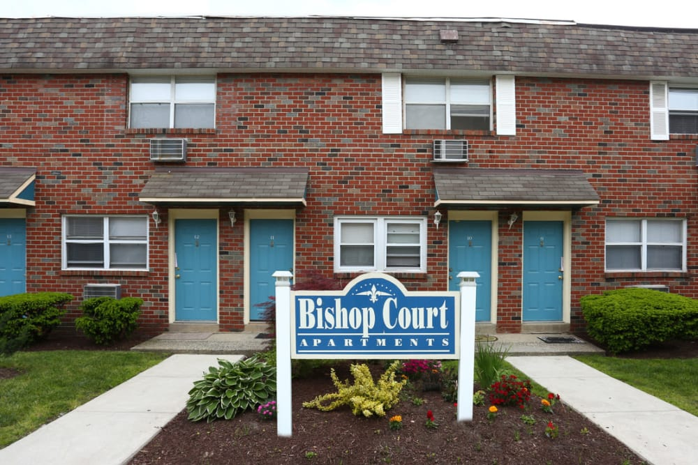 Apartment sign surrounded by beautiful landscaping at Bishop - Stratford Court Apartments in Stratford, New Jersey