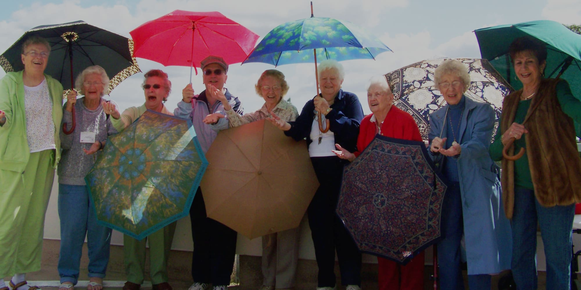 Residents from Hawthorn Senior Living in Vancouver, Washington with umbrellas, enjoying the weather