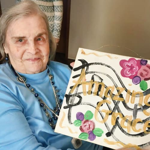 Residents displaying a music-themed painting with the text 'amazing grace' at The Oxford Grand Assisted Living & Memory Care in McKinney, Texas