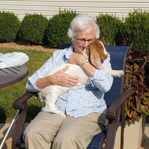 A resident sitting outside holding her dog at Alderbrook Village in Arkansas City, Kansas