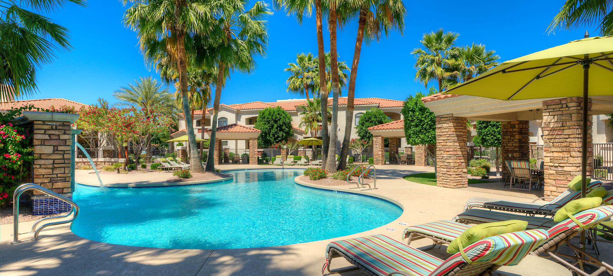 Luxurious swimming pool with lounge chairs at San Prado in Glendale, Arizona