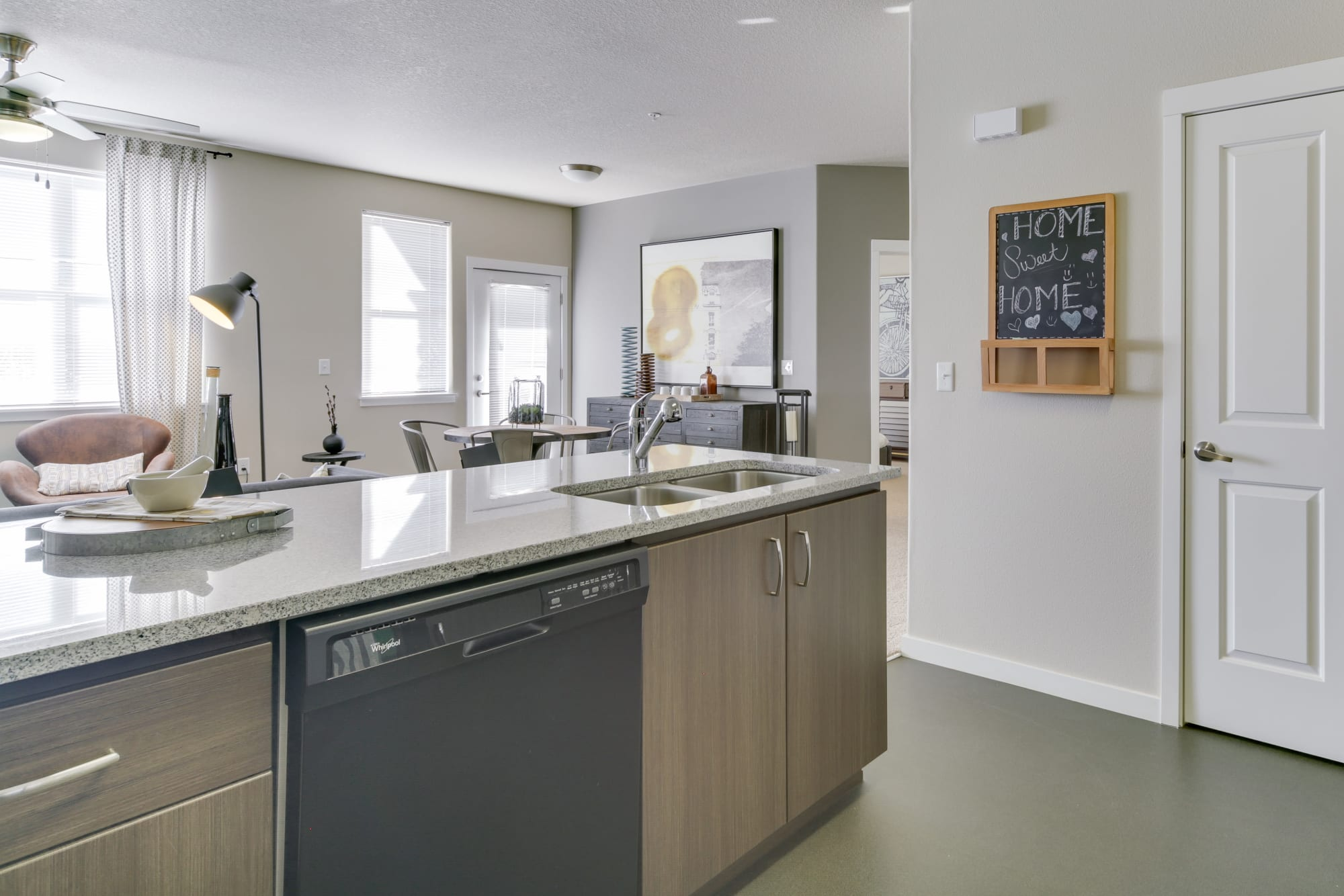 An open floor plan connecting kitchen and living area at Terrene at the Grove in Wilsonville, Oregon