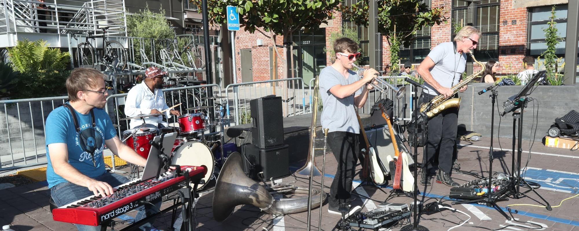 Friends playing music near The Moran in Oakland, California