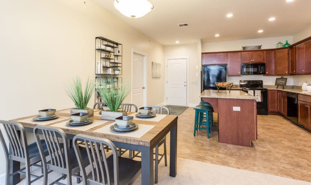 Dining table and kitchen at Gateway Landing on the Canal home in Rochester, NY