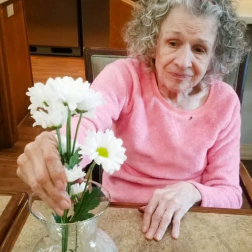 Resident placing some flowers in a vase at Glen Carr House Memory Care in Derby, Kansas