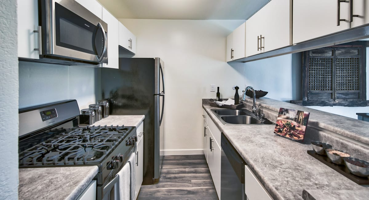 Granite countertops and stainless-steel appliances in a model apartment's kitchen at Mediterranean Village Apartments in Costa Mesa, California