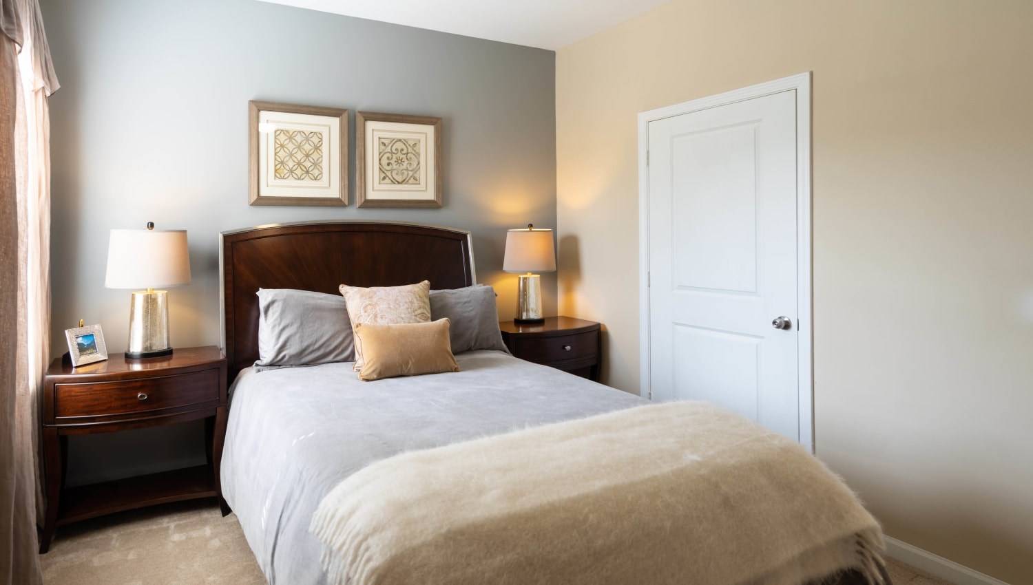 Model home's bedroom with a ceiling fan at Legends at White Oak in Ooltewah, Tennessee