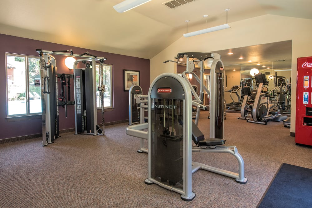 Fitness center with individual workout stations at La Valencia Apartment Homes in Campbell, California