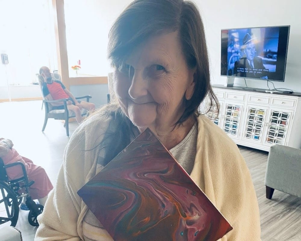 Resident showing off her artwork at Apple Creek Place in Appleton, Wisconsin.