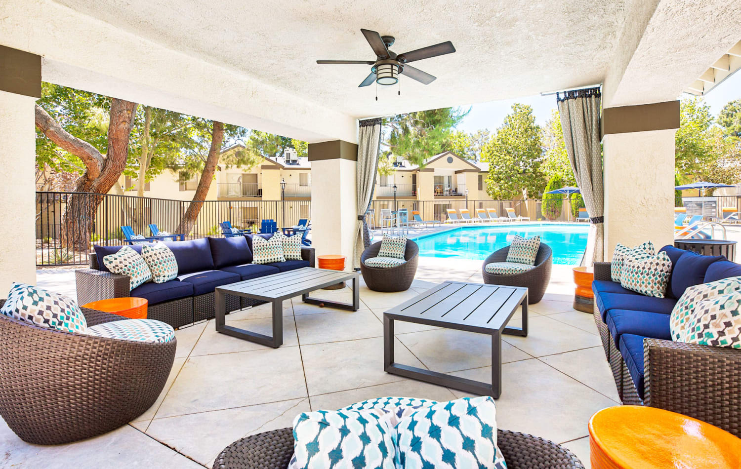 Covered outdoor lounge area with a ceiling fan near the swimming pool at Mountain Vista in Victorville, California