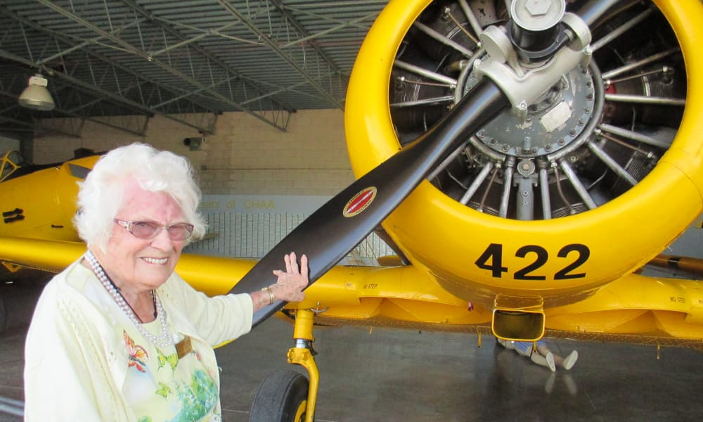 A resident from Cedarview Gracious Retirement Living in Woodstock, Ontario with her hand on a plane propeller