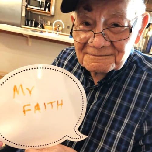 A resident holding a sign that says 'my faith' at Glen Carr House Memory Care in Derby, Kansas