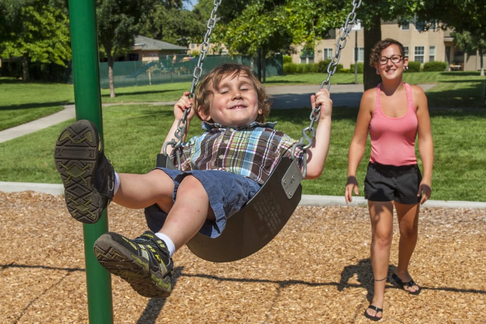 Resident and child playing on the swings at the playground at Oak Meadow Apartments in Chico, California