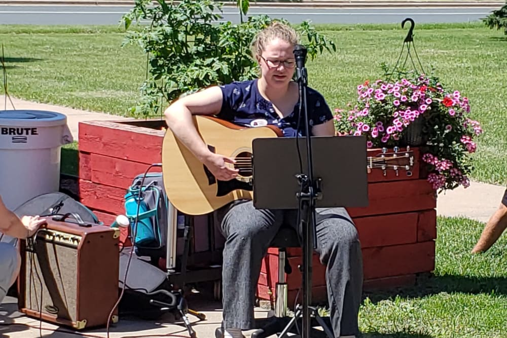 A woman plays live music on her guitar for residents at Landings of Blaine in Blaine, Minnesota