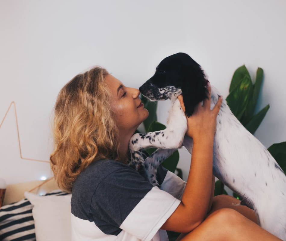 Resident giving her puppy a kiss in their new home at Veranda La Mesa in La Mesa, California