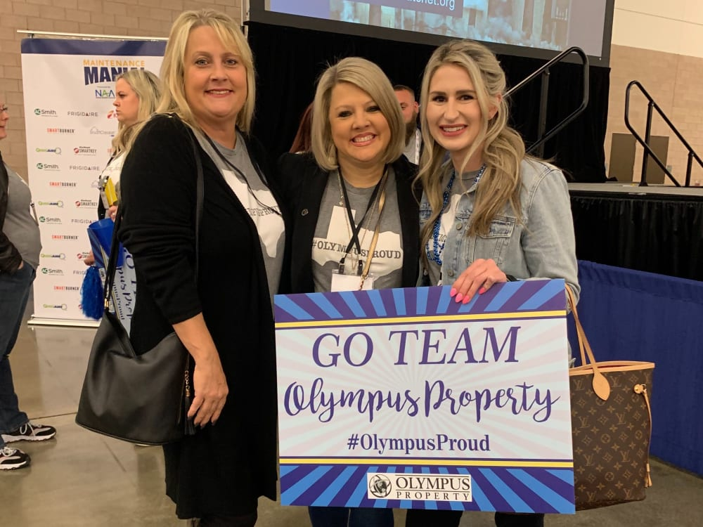 Employees posing for a photo at an event representing Olympus Property in Fort Worth, Texas