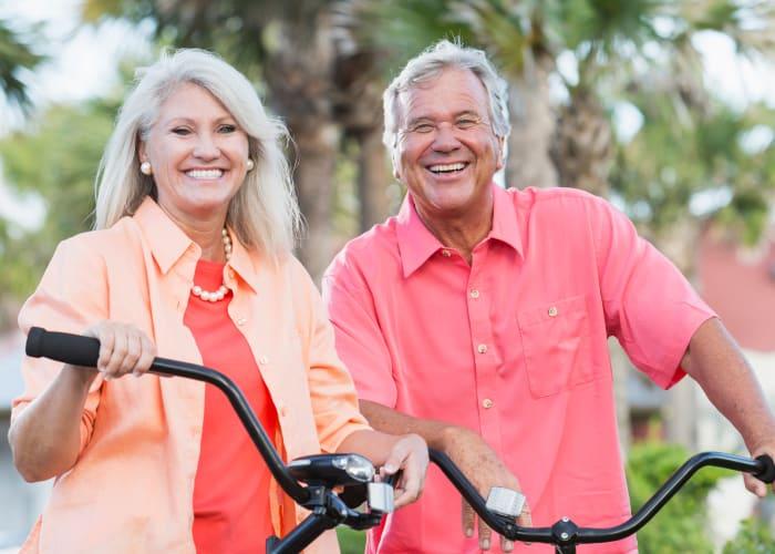 Seniors riding bikes at Avenida Palm Desert senior living apartments in Palm Desert, California