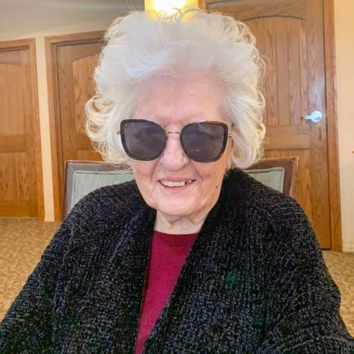 A smiling resident wearing sunglasses at Glen Carr House Memory Care in Derby, Kansas