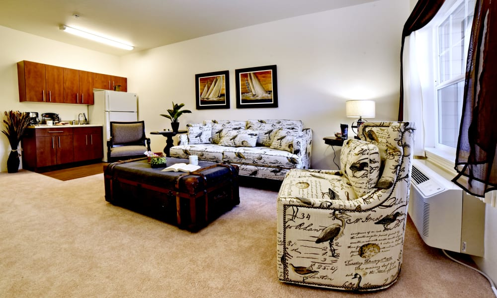 A spacious living room and open kitchen for residents at Linwood Estates Gracious Retirement Living in Lawrenceville, Georgia