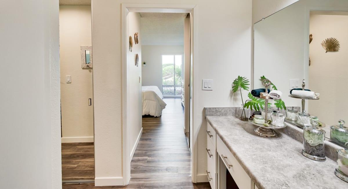 Primary bedroom's en suite bathroom with a spacious granite countertop and large vanity mirror in a model home at Mediterranean Village Apartments in Costa Mesa, California