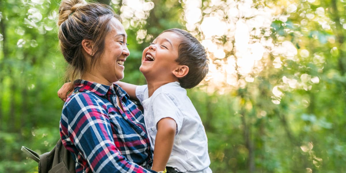 Resident holding and laughing with her son near The Fairmont at Willow Creek in Folsom, California
