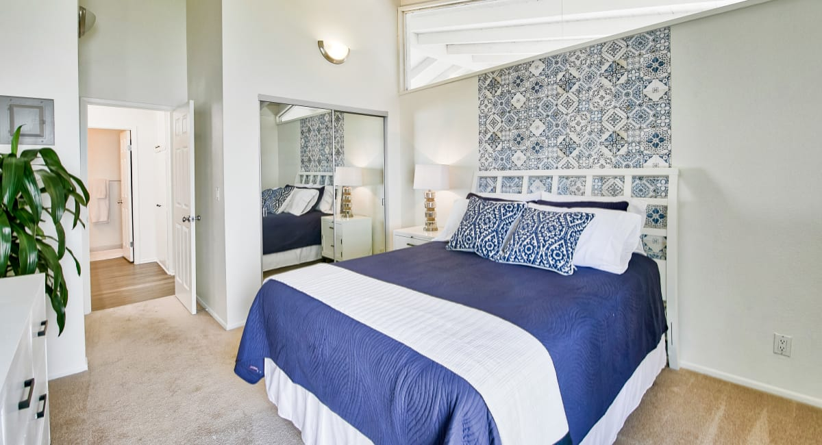 Well-furnished primary bedroom with an en suite bathroom in a model home at Mediterranean Village Apartments in Costa Mesa, California