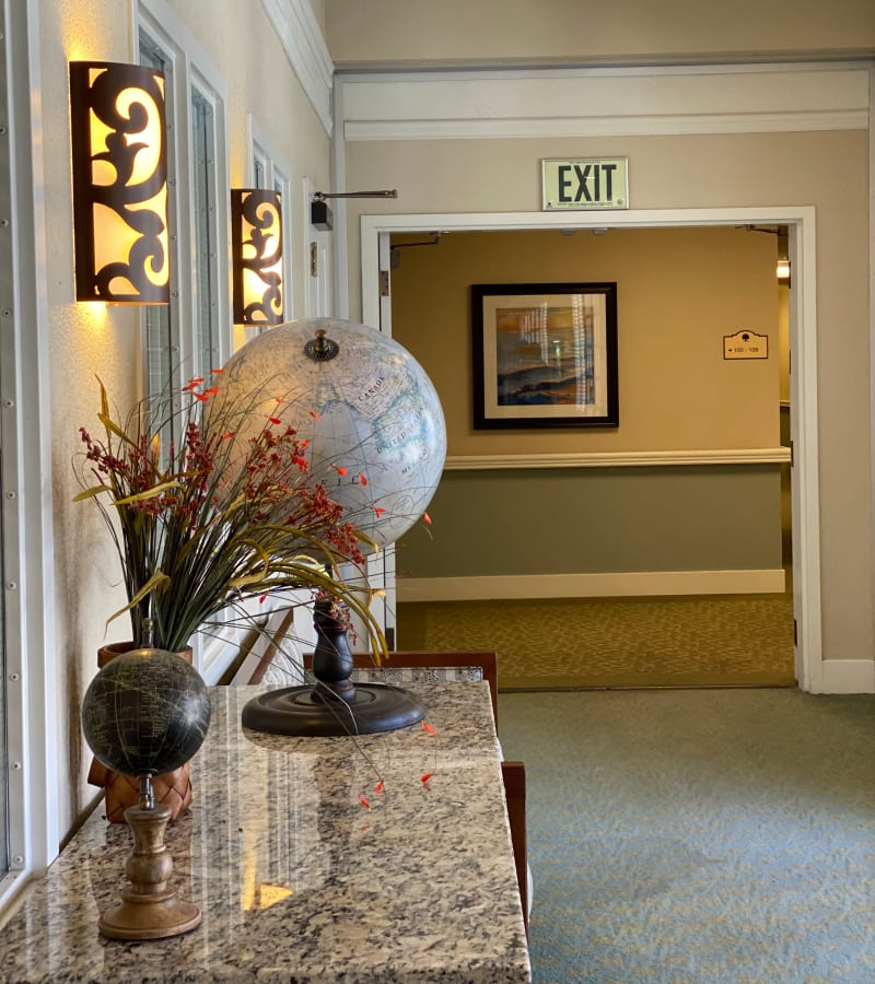 Hallway with globe at Pacifica Senior Living Fresno in Fresno, California.