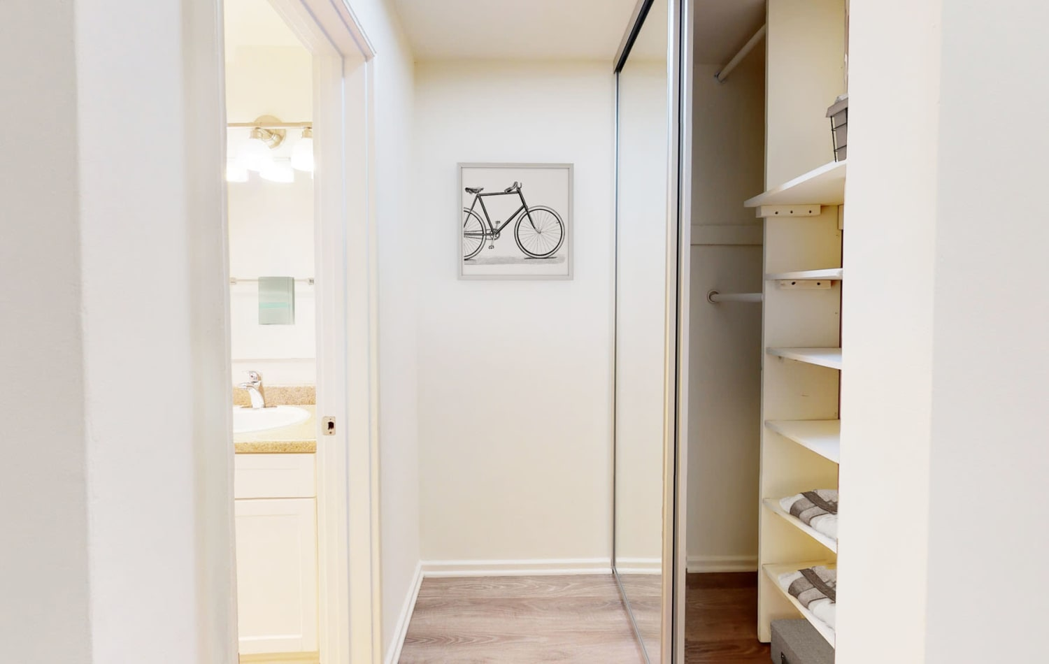 Mirrored closet doors and built-in shelving in a model two bedroom home's primary suite at West Park Village in Los Angeles, California