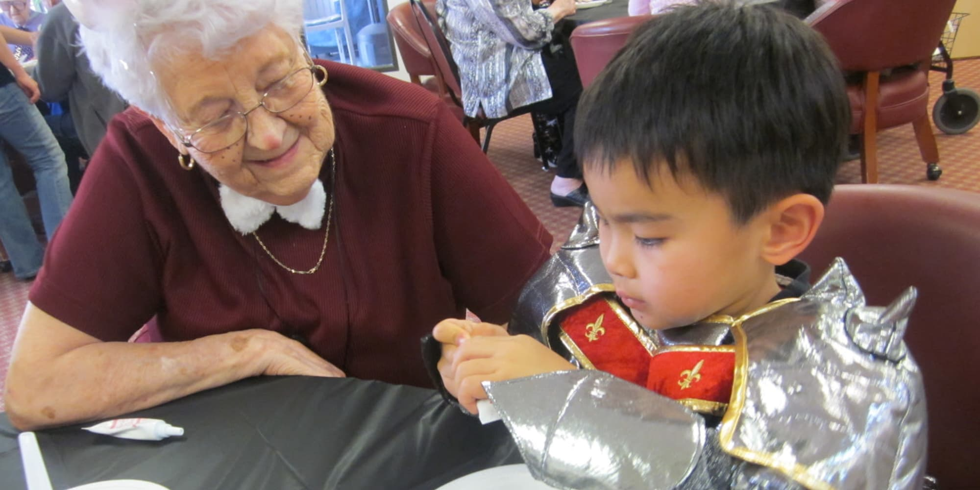 A resident decorating cookies with a child at Victoria Park Personal Care Home in Regina, Saskatchewan