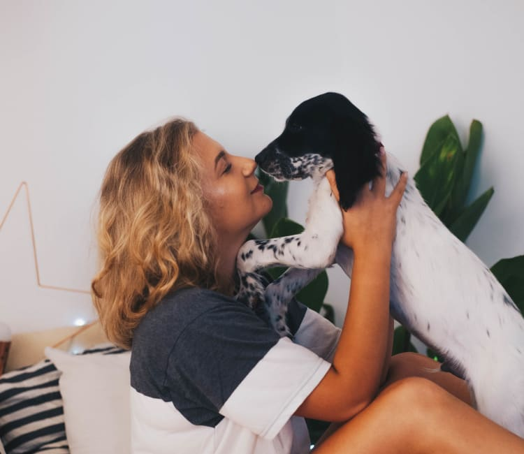 Resident giving her puppy a kiss in their new home at Sofi Sunnyvale in Sunnyvale, California