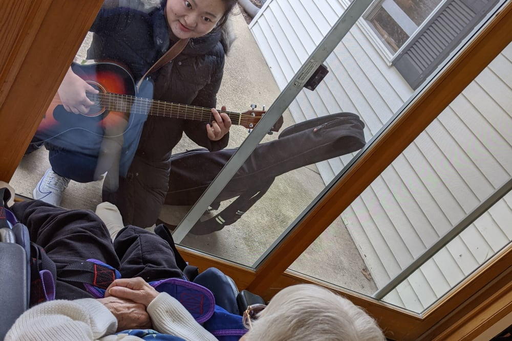 Staff serenades a resident through a window at Ramsey Woods in Cudahy, Wisconsin.