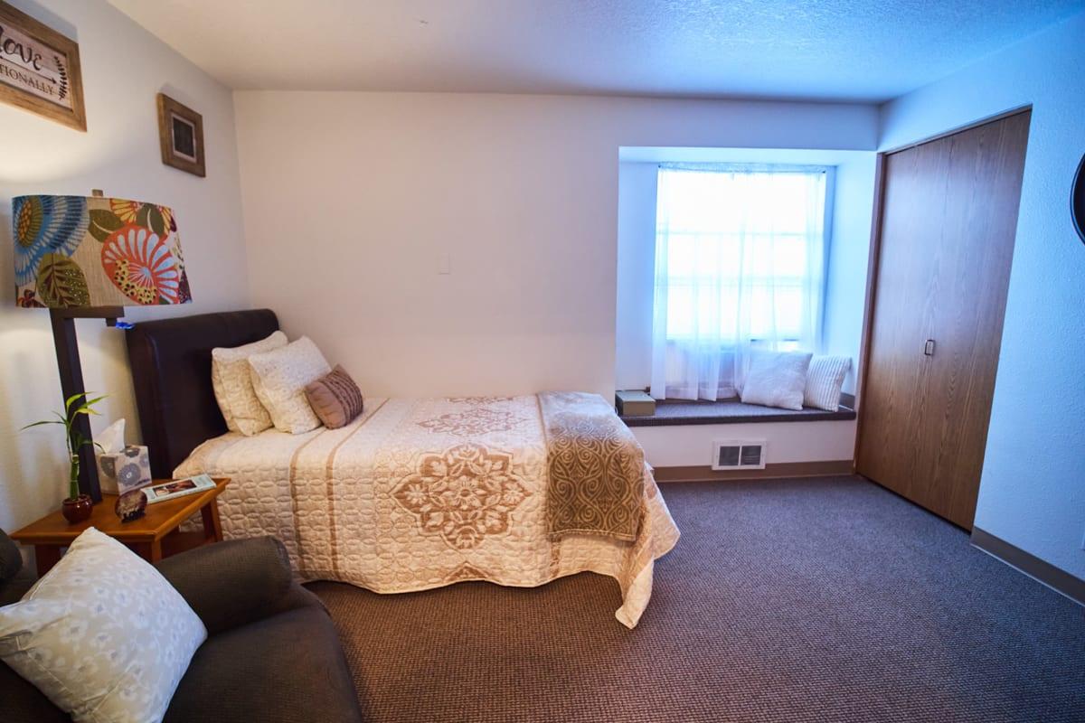 Studio senior apartment with a small bed at Farmington Square Beaverton in Beaverton, Oregon