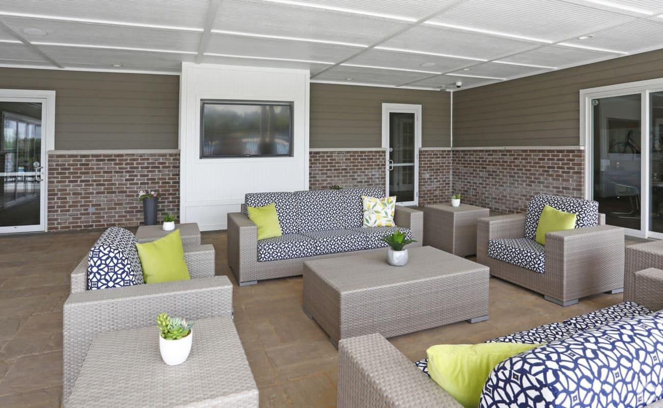 Shaded outdoor lounge with a flatscreen TV at Bonterra Apartments in Fort Wayne, Indiana