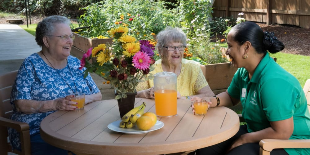 Residents enjoying a beverage with caregiver at The Springs at Willowcreek in Salem, Oregon