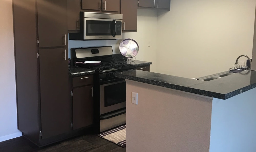 Dark cabinets and stainless-steel appliances in model kitchen at Cordova Park Apartment Homes