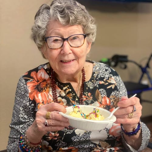 A resident smiling and eating a snack at FountainBrook in Midwest City, Oklahoma
